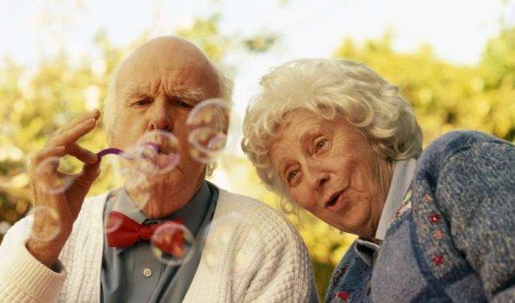 Пожилая пара играет с мыльными пузырями