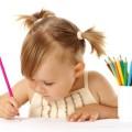 Малышка рисует цветным карандашом